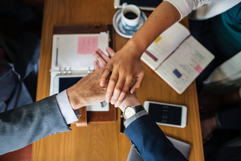 Three business man team joining hands together